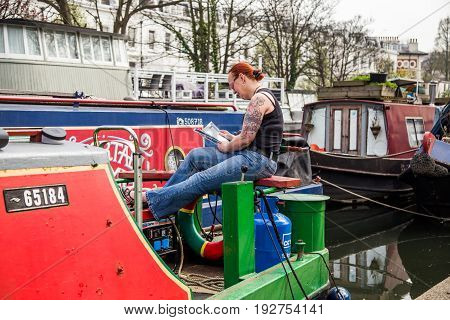 UK London - April 08 2015: Woman reading a book sitting on a barge. Regent's canal Little Venice in London