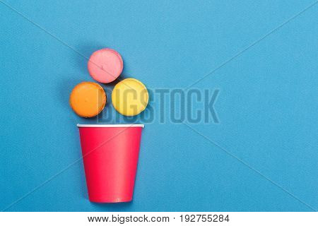 Colorful macaroons falling into red paper cup. Minimal concept. Appetizing macaroons on the blue background. Flat layout.