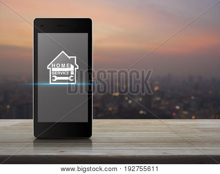 Hammer and wrench with house icon on modern smart phone screen on wooden table over blur of cityscape on warm light sundown Home service concept