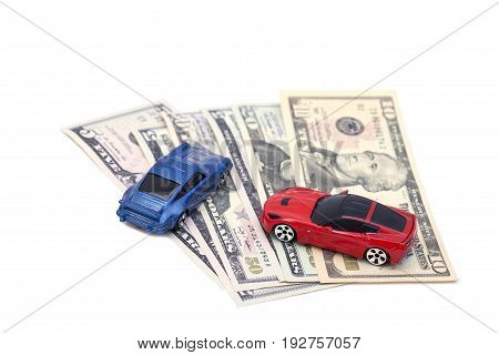 Red end blue toy cars on dollar banknotes isolated on white background