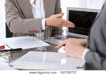 Group of business people or lawyers at meeting discussing contract papers. Woman pointing into laptop computer monitor.