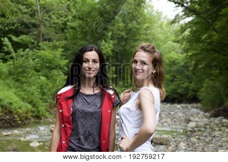 Girls Blonde And Brunette Against The Background Of A Mountain River And Forest. Posing Against The