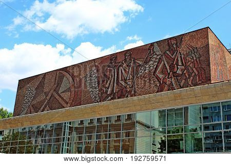 Moscow, Russia - August, 2017: Ceramic Soviet mosaic with hammer and sickle symbol and revolutionary on top of the building.