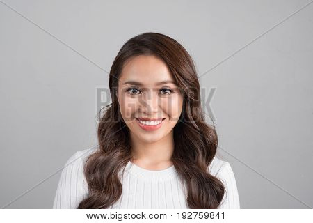 Close up portrait of smiling confident businesswoman looking straight isolated on grey background.