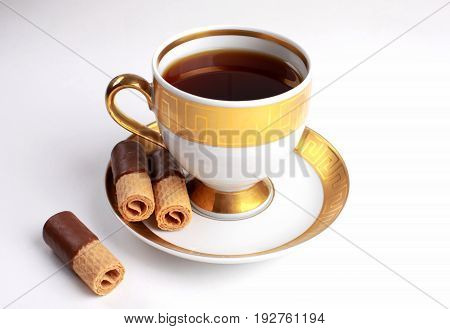 Traditional English tea - white and gold china cup of tea with chocolate wafers
