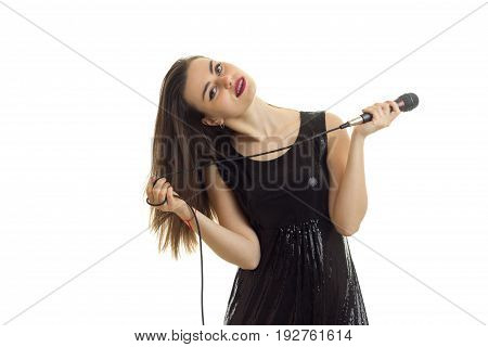 horizontal portrait of charming young singer with a microphone in her hand isolated on white background