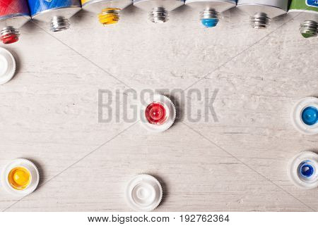 Tubes Of Paint On A Wooden Background,