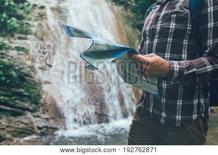 Unrecognizable Young Traveler With Backpack Is Standing By Waterfall And Looks At The Map Holidays And Tourism Concept