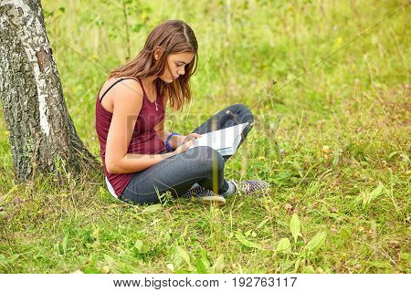 The Girl Is Reading A Book In The Park In The Summer