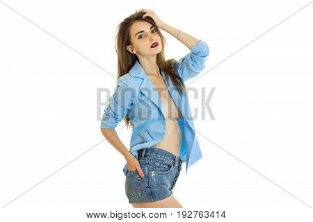 beautiful young model in a blue jacket and shorts posing in Studio isolated on white background