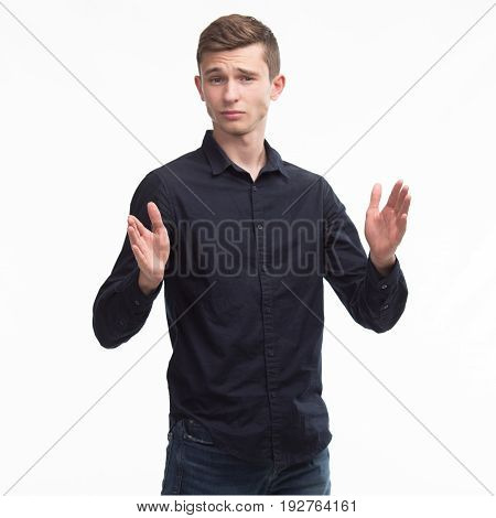 Young confident man showing width by hands on a gray background. Ideal for banners, registration forms, presentation, landings, presenting concept.