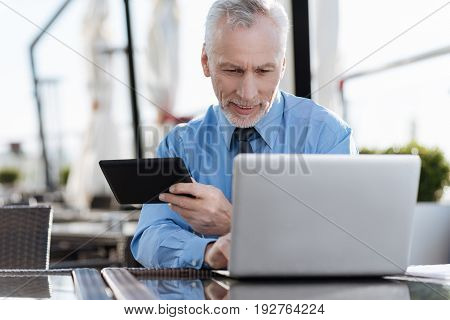 Write down the email. Handsome bearded businessman keeping smile on face and holding tablet in his hand while looking downwards