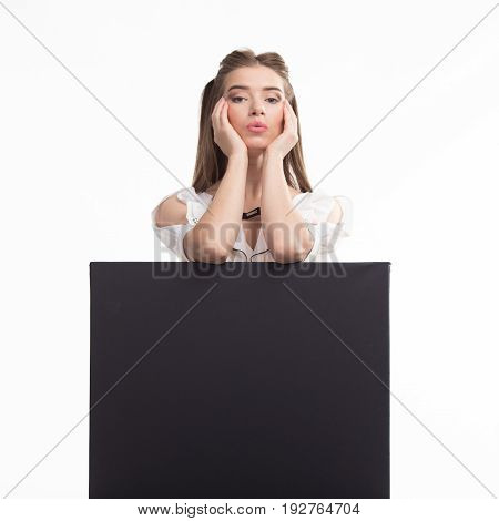 Young dreamy woman portrait of a confident businesswoman showing presentation, pointing placard black background. Ideal for banners, registration forms, presentation, landings, presenting concept..
