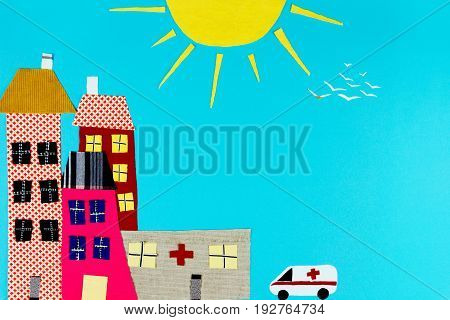 Fabric town. Houses trees and the sun and ambulance made of colorful pieces of fabric isolated on blue background.