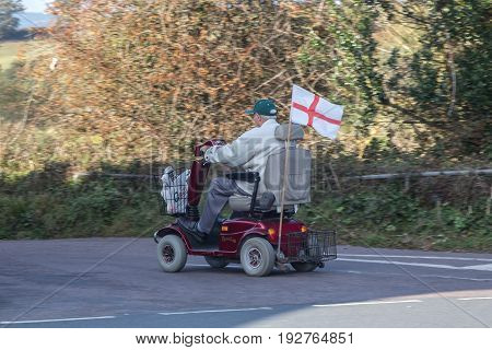Cockwood Devon England 21 October 2016: An elderly man with purchases rides on an electric scooter. The flag of England is attached to the scooter.