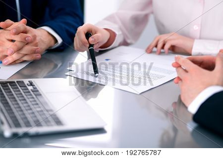 Group of business people and lawyers discussing contract papers sitting at the table, close up
