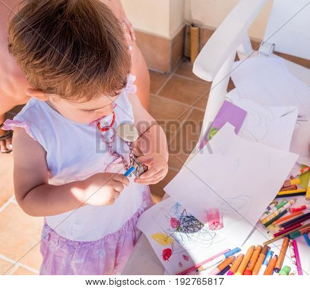 baby girl sharpening pencil sharpener playing with pastels blank sheet