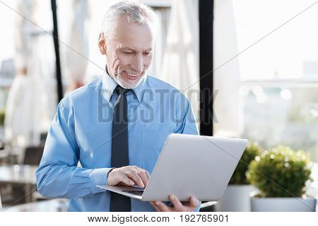 Express positivity. Happy man keeping smile on his face and holding computer in left hand while typing email