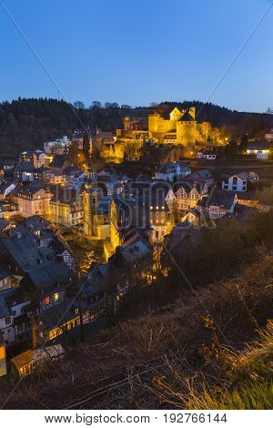 View from a hill over the beautiful Eifel village Monschau with its castle and night blue sky in Germany.