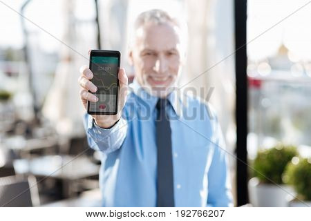 Financial market. Happy man holding phone in right hand while demonstrating it for everybody and looking straight at camera