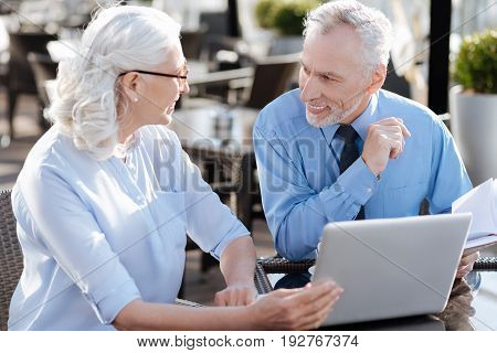 New in. Attractive female person sitting opposite her partner, leaning left elbow on the table while touching computer