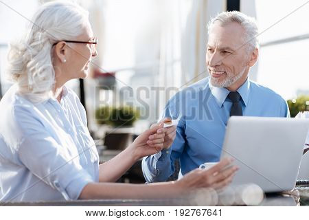 Offer your idea. Pretty blonde sitting in semi position and looking at her colleague while giving him gold card