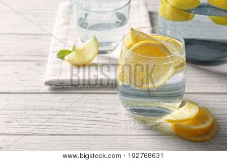 Glass of cold lemon water on light wooden table