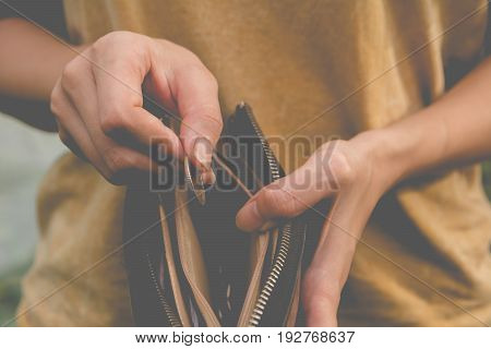 Close-up woman standing and holding money coin with wallet empty of money