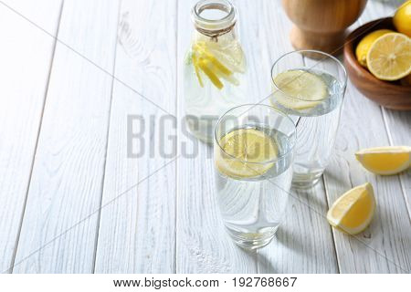 Composition with cold lemon water on light wooden table