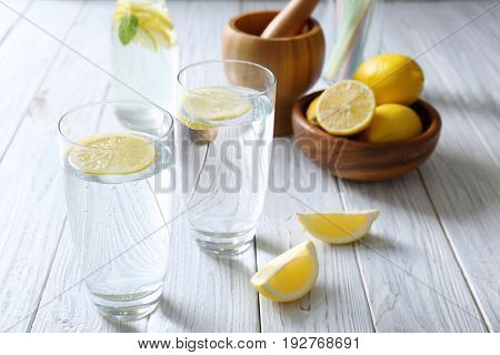Glasses with cold lemon water on light wooden table