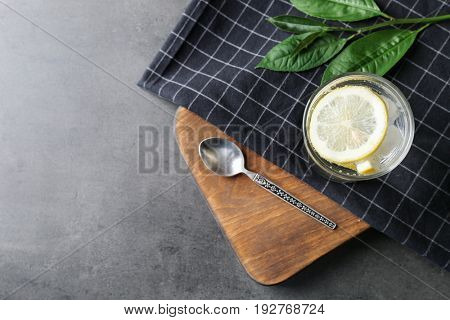 Composition with cold lemon water on grey table