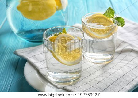 Composition with cold lemon water on wooden table, closeup