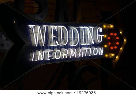 A neon arrow points the way to wedding information.