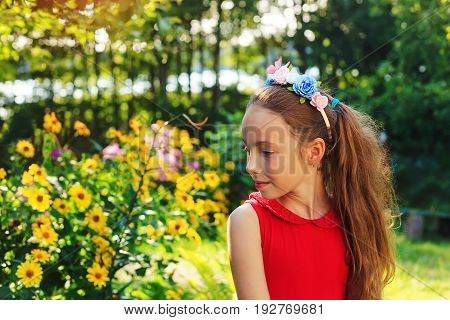 Cute teen girl is sitting and dreaming at the garden in warm sunny summer day