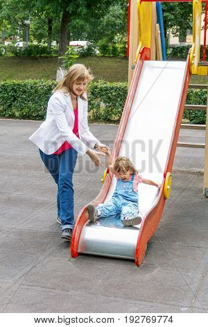 Mother with baby girl riding on hutches with screw up one eyes