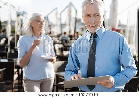 Keep calm and smile. Confident bearded worker holding folder with documents in both hands and standing on the foreground