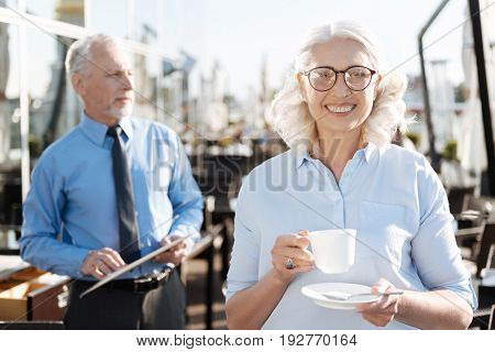 Pause in office. Amazing female posing with cup in hands while wearing stylish glasses and feeling happiness