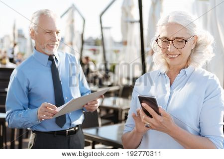 Feeling good. Attentive woman keeping smile on her face and looking at screen of phone while standing on the foreground