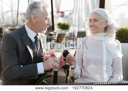 Best day. Positive delighted man sitting in semi position and holding nice posy in left hand while touching glasses with his sweetheart