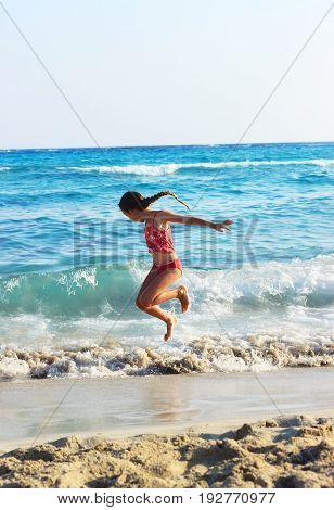 Happy Little Girl Jumping In Sea Waves. Jump Accompanied By Water Splashes. Summer Sunny Day Ocean Coast
