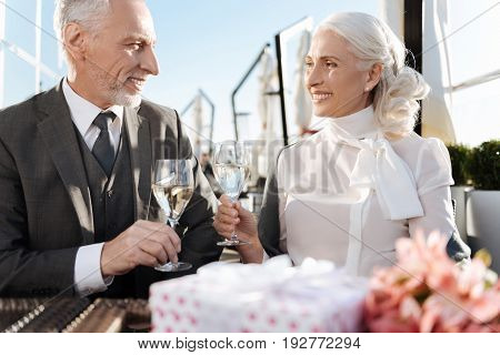 Great pleasure. Positive delighted loving couple feeling happiness while spending time together and drinking champagne