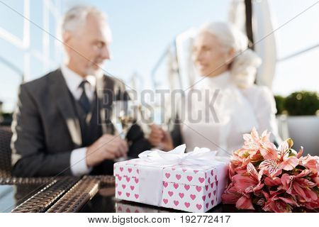 It is surprise. Beautiful woman sitting near her cavalier in restaurant and looking at each other while feeling happiness