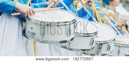 Drummers in blue uniform stand in a row and drumming
