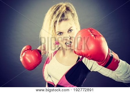 Sporty angry determined woman wearing red boxing gloves fighting. Studio shot on dark background.