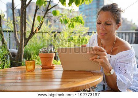 Woman on rooftop websurfing on digital tablet