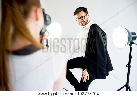 Professional photographer working at studio with a model