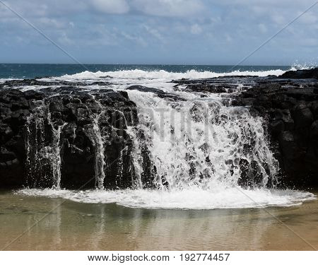 Strong surf and waves break over the rocks at Lumahai beach frozen to look like milk