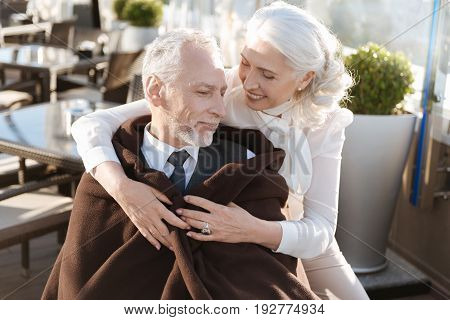 Listen to my words. Positive delighted blonde standing behind her man and bowing head while keeping smile on face