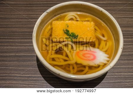 Kitsune Udon Japanese Noodles In White Bowl On Wooden Table
