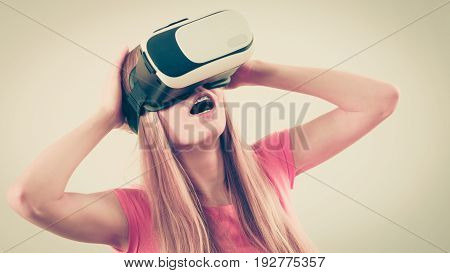 Young woman wearing virtual reality goggles headset vr box. Studio shot on gray